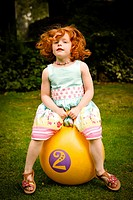 Little girl, aged 5, bouncing on a space hopper, in a summer garden