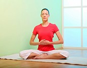 solar plexus breathing . Young woman is sitting cross_legged and holding her hands in front of her stomach