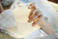 The hand of an elderly woman is holding a mug made of plastic