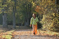 Young Woman Nordic Walking on a sunny autumn afternoon