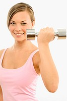 A blonde woman holds the dumbbell as she smiles at the camera