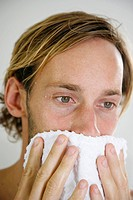 Young man drying his face with a towel _ close_up _ portrait