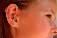 close up _ ear of little girl with hearing aid _ acoustic hearing apparatus _ hearing device