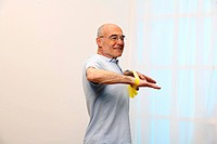 older man is training his shoulders with a stretch_band _ senior _ muscularity _ compress the scapulas