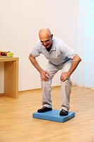 older man is doing gymnastics _ senior is doing knee bending on instable pad _ balance