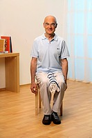 older man sitting on a chair doing knee exercises _ senior doing gymnastics _ less pain