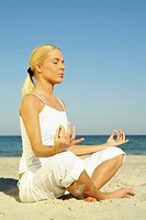 Young blond woman sitting on the beach doing yoga