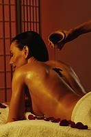 Young dark_haired woman lying on a massage_bench getting a hot_chocolate treatment