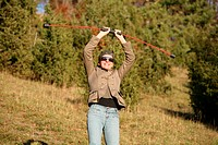 woman holding a flexibar standing at the edge of the forest