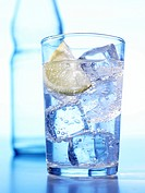 Glassware with H20, icecubes and a lemon pane in the background a bottle. H2O H20 _ CO2 Carbonic acid _ ascorbic acid
