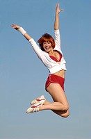 young adult woman does jumps in the air in Athletic wear