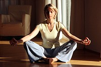 Young adult woman meditates in typical Yoga_attitude