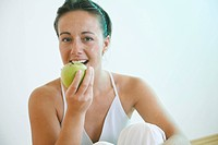 Young woman eating an apple.