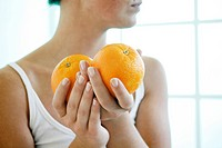 Female hands holding two oranges.