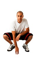 Sporty handsome African Hispanic guy crouching and hand on floor, isolated