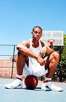 Handsome sporty African_American male basketball player with attitude dressed in white sitting on his ball outdoor on a summer day in a basketball cou...