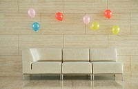 an empty sofa and balloons on the wall