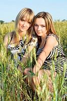 Two smiling pretty girlfriends sitting in field