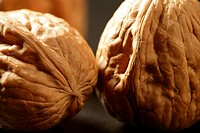 Three walnuts with shells over black background