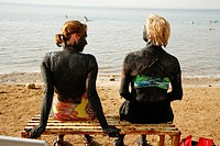 People covered with mud at the dead sea, Jordan