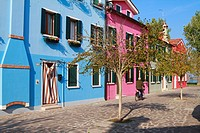 A cyclist rides past colourfully painted houses, Burano, Venice, Veneto, Italy, Europe