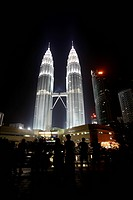 people enjoy the sign of the night scene of the Petronas Twin Towers