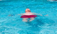 Senior retired man swimming in pool