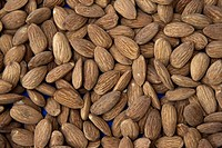 A close up to almonds on a counter in an open marketplace