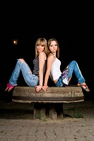 Two attractive girls sitting on a stone bench