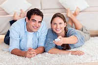 In love couple watching TV while lying on a carpet