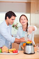 Portrait of a couple making fresh fruits juice in their kitchen