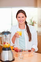 Portrait of a young woman drinking fresh fruits juice in her kitchen