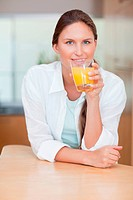Portrait of a smiling woman drinking juice in her kitchen