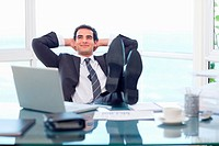Smiling businessman relaxing in his office