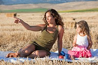mother and daughter having a picnic in the field