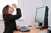 Detail of young business person woman applying eye drops on workplace _ computer on table