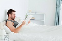 Serene man reading a newspaper in his bedroom