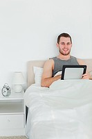 Portrait of a handsome man using a tablet computer in his bedroom