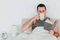 Man reading a book while holding a cup of coffee in his bedroom