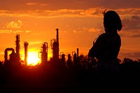 Woman looks on oil refinery at sunset silhouette