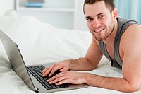 Handsome man using a laptop while lying on his belly in his bedroom