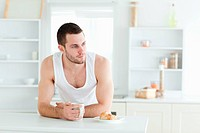 Handsome man having breakfast in his kitchen