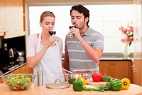 Young couple drinking a glass of wine in their kitchen