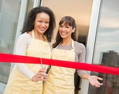 Two female business owners cutting red ribbon