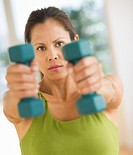 Mid adult woman training with dumbbell