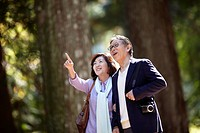 Senior Couple Walking in Park and Pointing