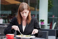 The Netherlands, Amsterdam, Businesswoman eating salad in sidewalk cafe