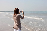 Woman on beach using camera