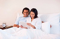 Young couple surfing the internet on the bed