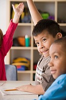 Children 6_7 raising hands in classroom